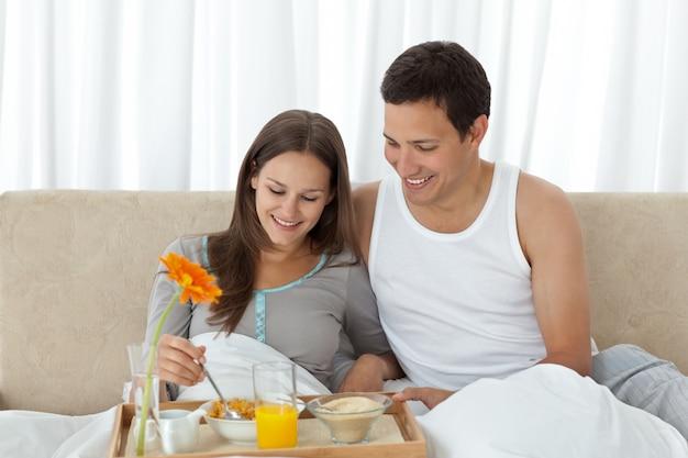 Jovem, tomando café da manhã na cama com o namorado