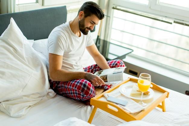 Jovem tomando café da manhã na cama e lendo jornal no quarto