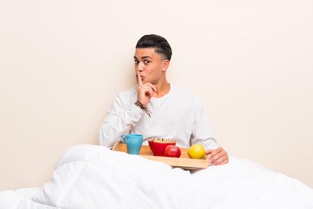 Jovem tomando café da manhã na cama, fazendo o gesto de silêncio