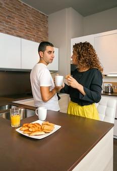 Jovem tomando café da manhã rápido em casa com uma mulher pronta para ir ao escritório