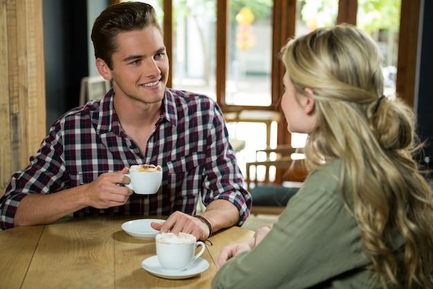 Jovem tomando café enquanto fala com uma mulher no café