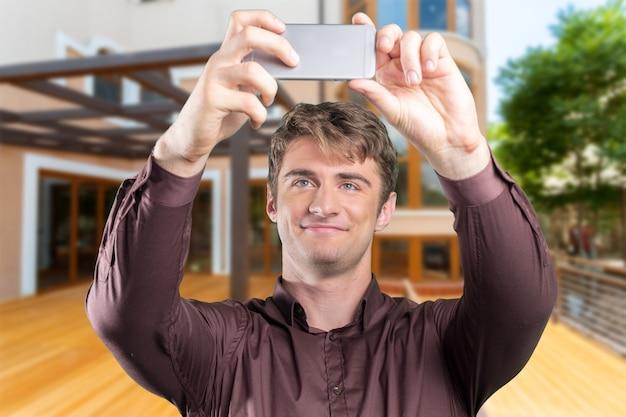 Jovem tomando selfie com seu smartphone. close-up tiro