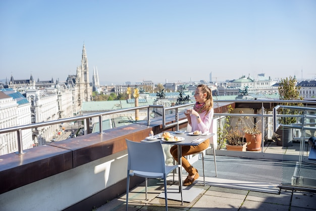 Jovem tomando um café da manhã servido em um telhado do edifício da cidade europeia