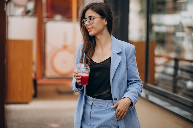Jovem tomando uma bebida gelada fora da rua