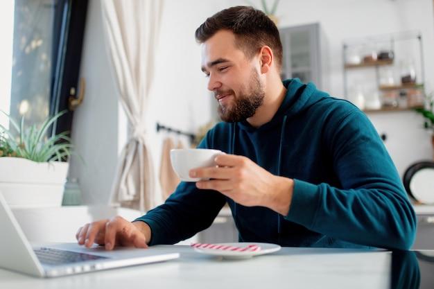Jovem trabalha em um computador em sua cozinha e bebe chá