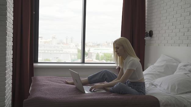 Jovem trabalha em um laptop em um quarto aconchegante e bem iluminado. a mulher loira está digitando no teclado no contexto de uma grande janela. conceito de trabalho remoto. 4k uhd