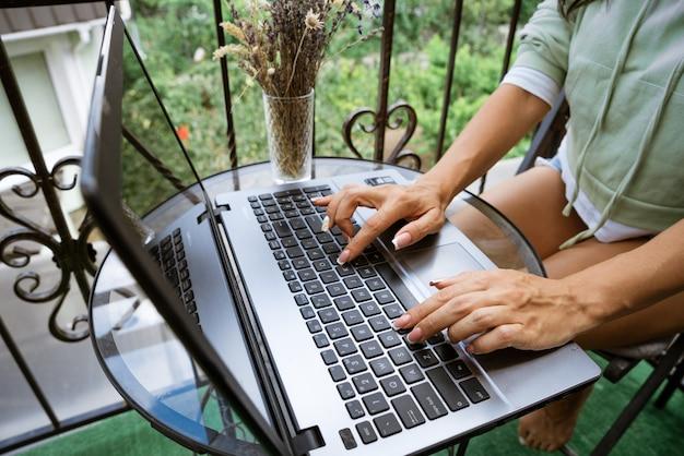 Jovem trabalha em um laptop no terraço conceito de trabalho remoto