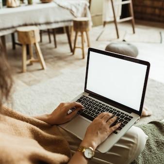 Jovem trabalha no laptop com tela em branco com espaço de cópia. design de interiores de salas de estar modernas