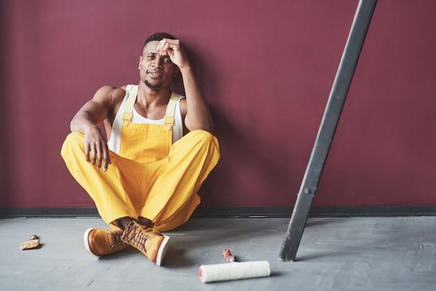 Jovem trabalhador afro-americano de uniforme amarelo tem um emprego
