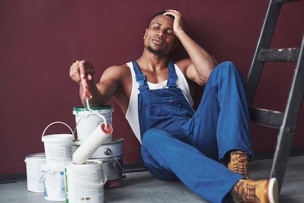 Jovem trabalhador afro-americano de uniforme azul faz uma pausa no trabalho