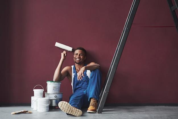 Jovem trabalhador afro-americano de uniforme azul faz uma pausa