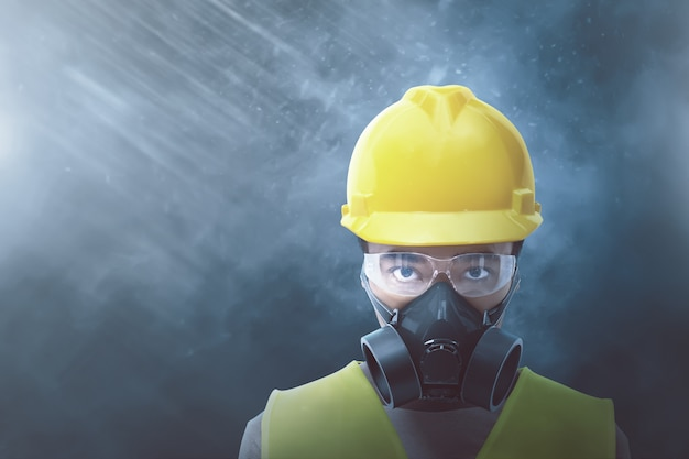 Jovem trabalhador asiático com capacete amarelo e máscara protetora
