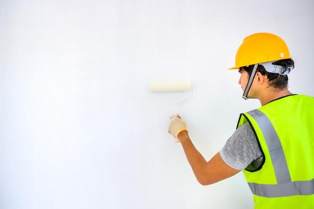 Jovem trabalhador asiático como pintor, para pintar as paredes da casa e usar um rolo para pintar o primer branco no canteiro de obras