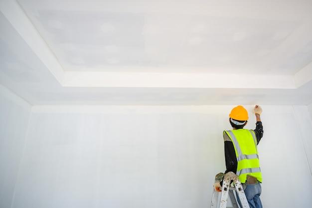 Jovem trabalhador asiático pinte o teto dentro de casa e use um rolo para pintar a base branca no canteiro de obras.