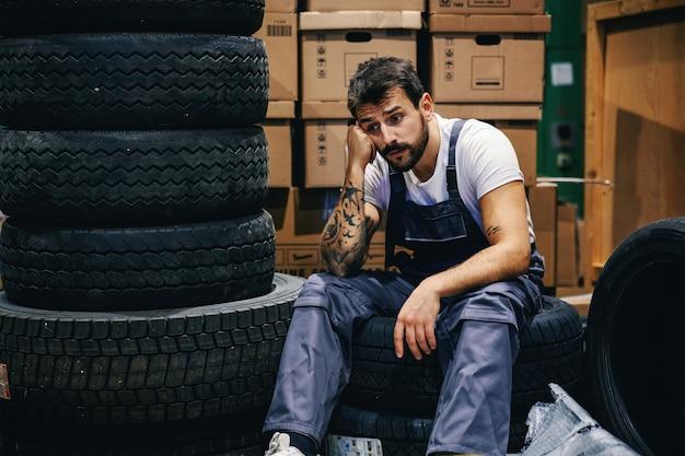 Jovem trabalhador barbudo tatuado e entediado de macacão sentado sobre os pneus no depósito de uma empresa de importação e exportação e aguardando ordens de seu chefe.