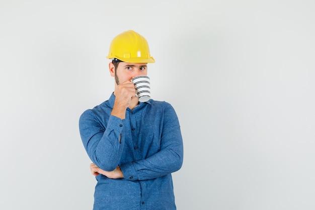 Jovem trabalhador bebendo café enquanto pensa na camisa, capacete
