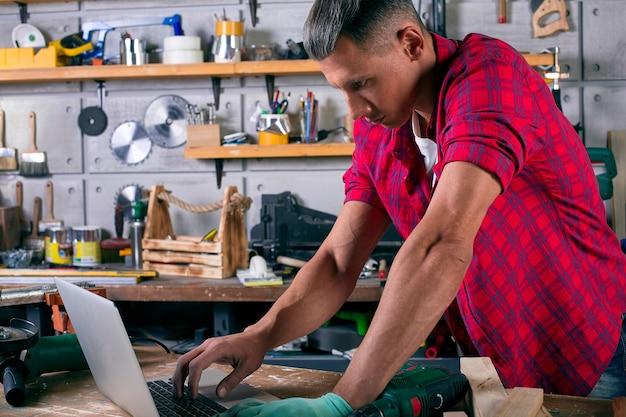 Jovem trabalhador bonito e confiante em geral usando cinto de ferramentas em pé na oficina