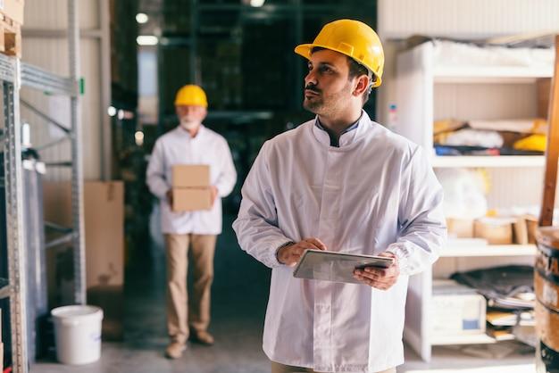 Jovem trabalhador caucasiano do sexo masculino usando tablet em pé no armazém.