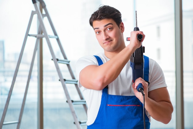 Jovem trabalhador com broca de mão