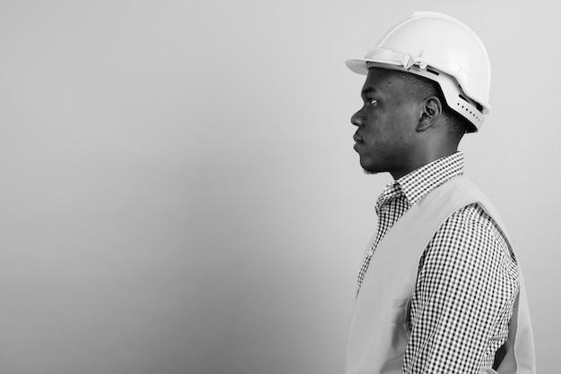 Jovem trabalhador da construção civil africano contra uma parede branca. preto e branco