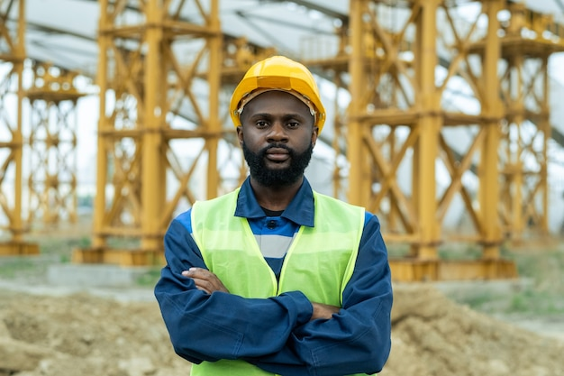 Jovem trabalhador da construção civil africano de uniforme e capacete de segurança cruzando os braços no peito