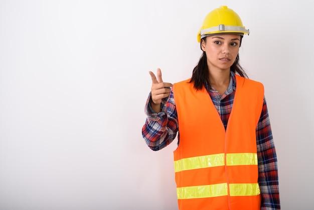 Jovem trabalhador da construção civil asiática apontando para o lado contra o espaço em branco