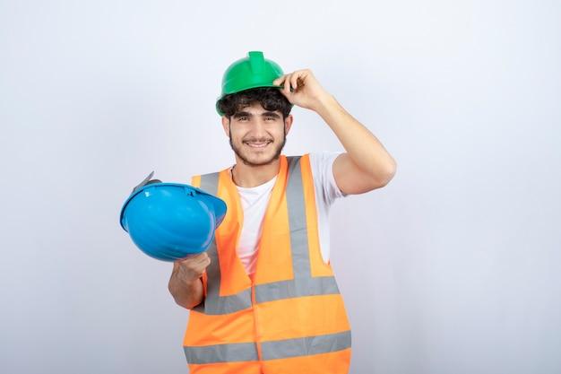 Jovem trabalhador da construção civil com capacete de segurança em pé sobre fundo branco. foto de alta qualidade