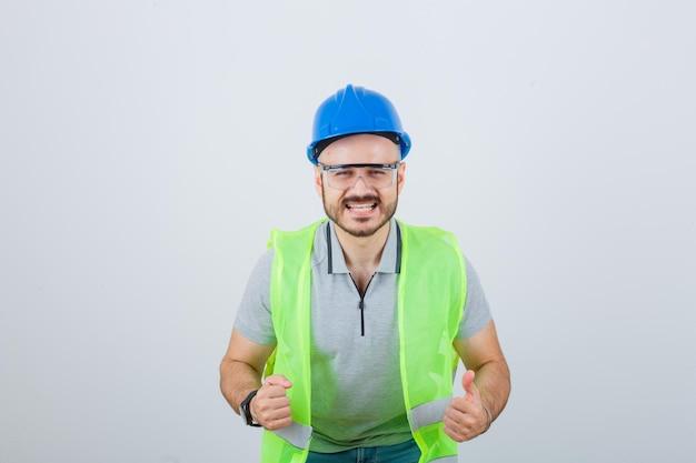 Jovem trabalhador da construção civil com um capacete de segurança e óculos