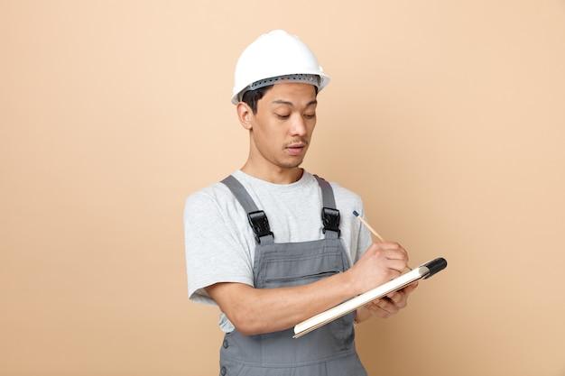 Jovem trabalhador da construção civil concentrado usando capacete de segurança e uniforme, escrevendo com lápis no bloco de notas