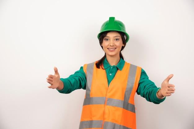 Jovem trabalhador da construção civil feminino em fundo branco.
