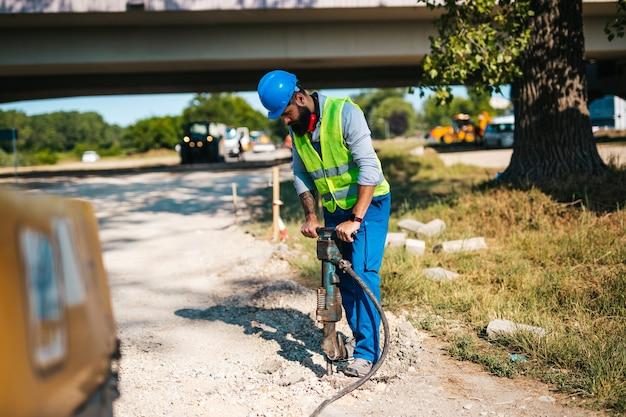 Jovem trabalhador da construção civil rodoviária em seu trabalho. dia de sol brilhante. luz forte.