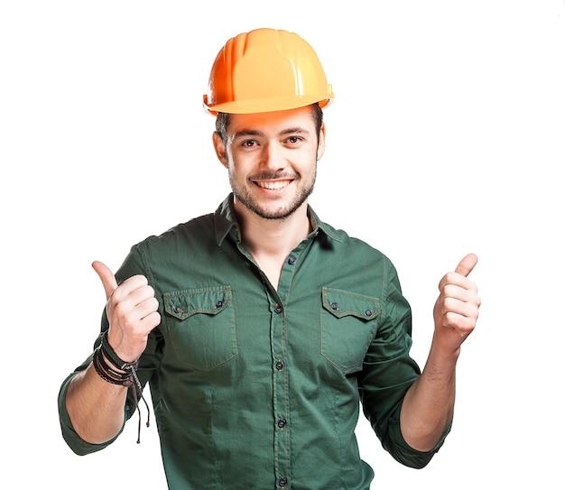 Jovem trabalhador da construção civil usando capacetes em uma parede branca