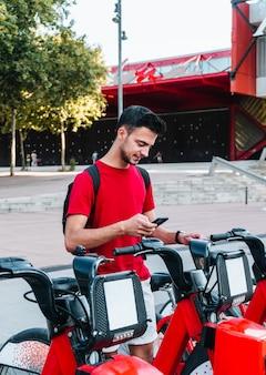 Jovem trabalhador de escritório, caucasiano, alugando uma bicicleta com seu telefone inteligente