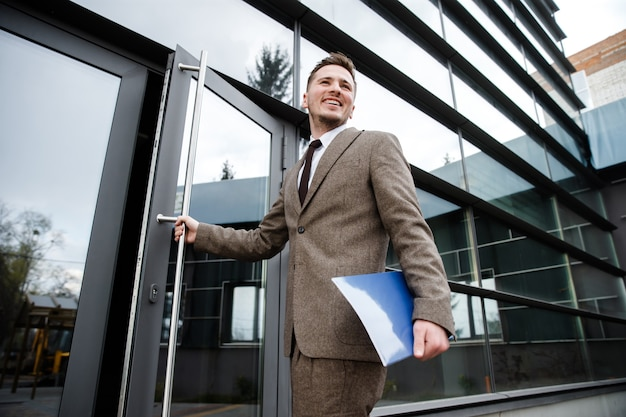 Jovem trabalhador de escritório entrando no prédio com uma pasta na mão