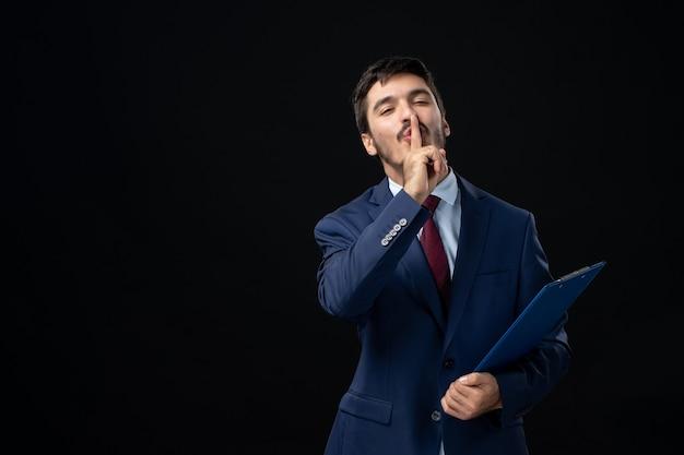 Jovem trabalhador de escritório masculino confiante em terno segurando documentos e fazendo gesto de silêncio na parede escura isolada