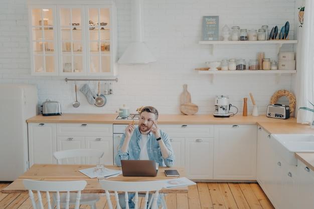 Jovem trabalhador de escritório trabalhando remotamente de casa com computador, sentado à mesa da cozinha, com a tarefa de um projeto importante, tentando encontrar uma solução, escrevendo e fazendo anotações