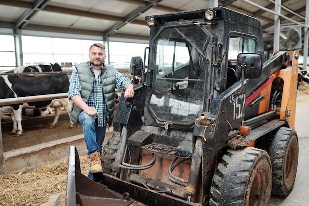 Jovem trabalhador de uma casa de fazenda em pé ao lado de um trator enquanto limpa o corredor de uma fazenda de animais entre duas fileiras de gado