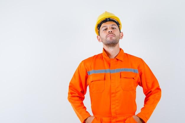Jovem trabalhador de uniforme de mãos dadas na cintura e parecendo confiante.