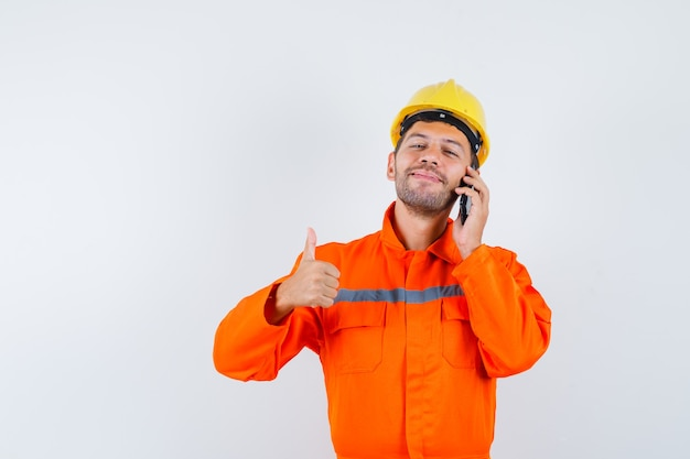 Jovem trabalhador de uniforme falando no celular, aparecendo o polegar e olhando alegre.