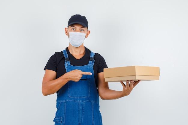 Jovem trabalhador de uniforme, máscara apontando para caixa de papelão, vista frontal.