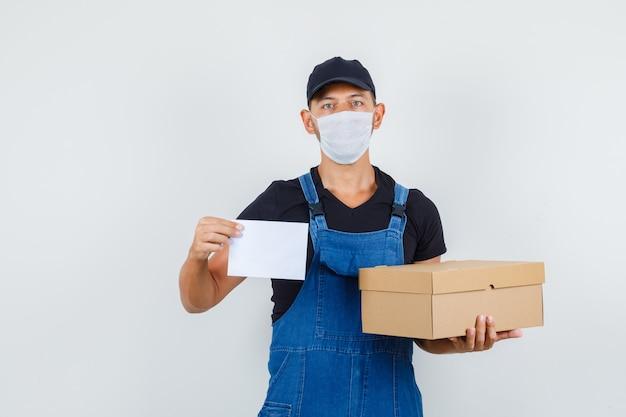 Jovem trabalhador de uniforme, máscara segurando uma caixa de papelão e uma folha de papel, vista frontal.