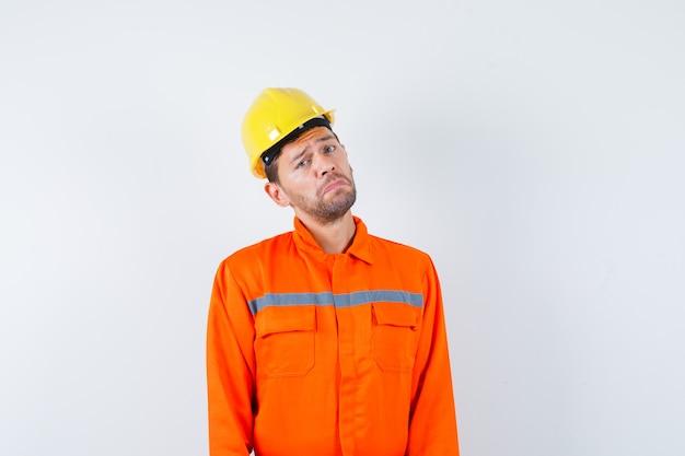 Jovem trabalhador de uniforme, olhando para a frente e parecendo humilde.