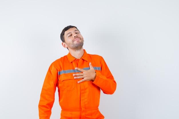 Jovem trabalhador, de uniforme, segurando a mão no peito e parecendo grato.