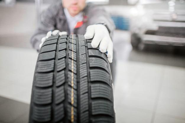 Jovem trabalhador detém pneu com ambas as mãos. ele usa luvas brancas. profissional é sério e concentrado. ele trabalha no salão.