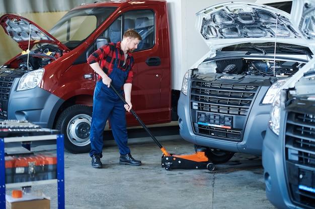 Jovem trabalhador do centro de serviço de reparo colocando o carrinho sob o carro antes do check-up técnico