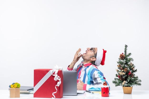 Jovem trabalhador do sexo masculino de vista frontal sentado em seu local de trabalho no fundo branco