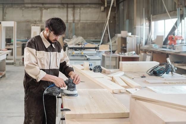 Jovem trabalhador do sexo masculino em roupas de trabalho e óculos de proteção, usando máquina de moer para processar superfície de placa de madeira na bancada de trabalho