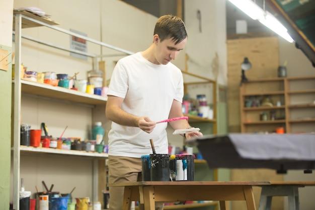 Jovem trabalhador do sexo masculino escolhendo as tintas apropriadas