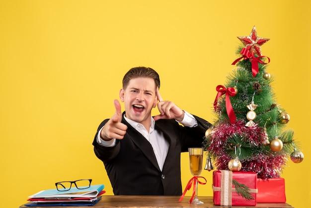 Jovem trabalhador do sexo masculino sentado com uma árvore e presentes de natal