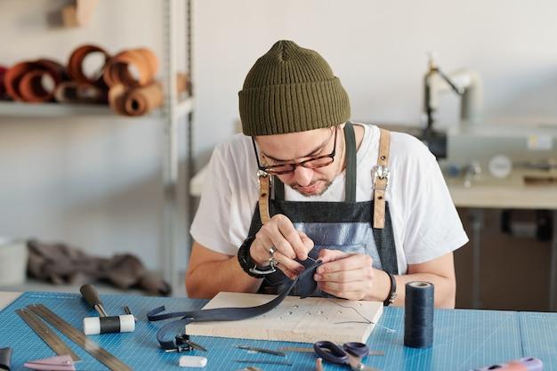 Jovem trabalhador em couro criativo curvando-se sobre a mesa enquanto costura um novo item de couro preto sobre uma placa de madeira na oficina